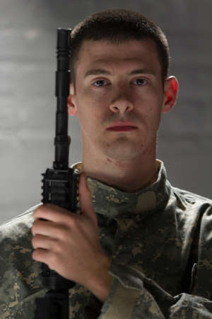 Young soldier posing with assault rifle, vertical Stock Photo