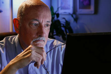 Older man studying information on his computer