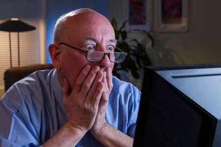 Older man shocked as he reads his computer monitor, horizontal