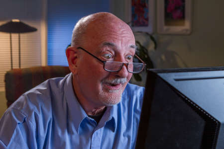 Older man excited while reading on computer, horizontal  Stock Photo