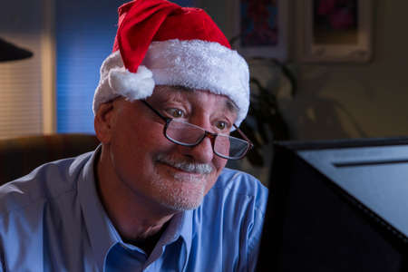Older man in Santa hat looks happy while reading off his computer monitor
