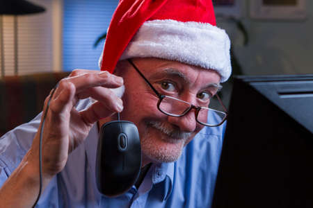 Older man in Santa hat Christmas shopping online,holding computer mouse photo