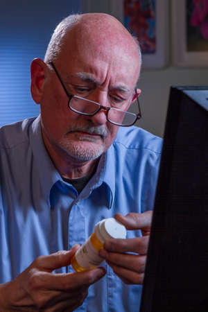 Older man examining prescription bottle, vertical