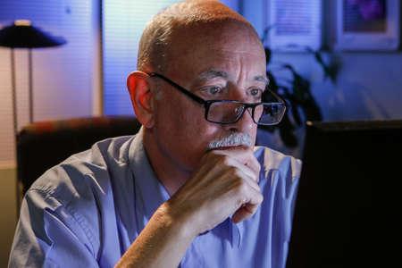 Older man using computer at home, horizontal  Stock Photo