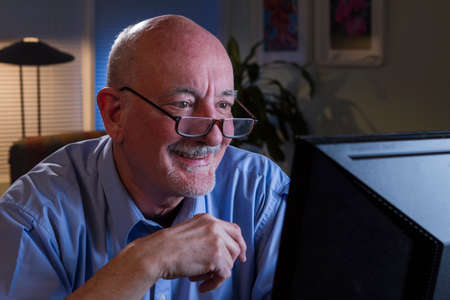 Older man reacts while reading content on computer monitor  Stock Photo