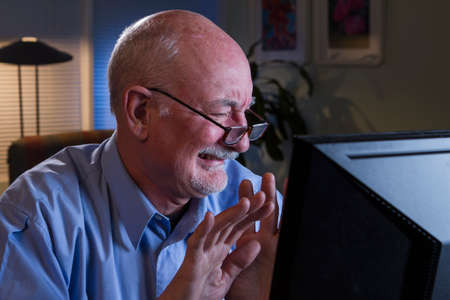 Older man disgusted at information on his computer monitor  Stock Photo
