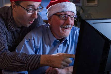 Men in Santa and elf hat using computer together, horizontal
