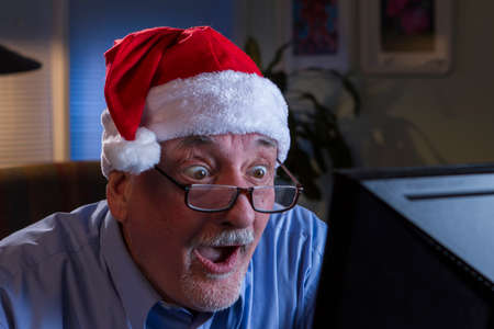 Older man in Santa hat looking shocked while on computer