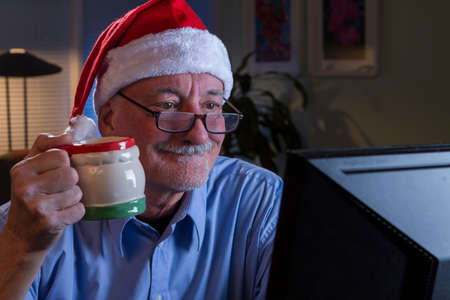 Older man in Santa hat Christmas shopping online, horizontal photo