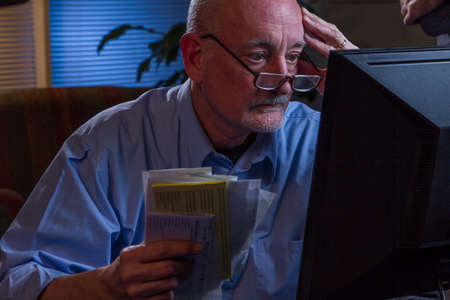 Stressed older man paying bills online, horizontal