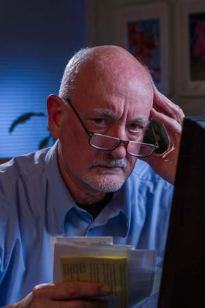 Stressed older man paying bills online, vertical  photo