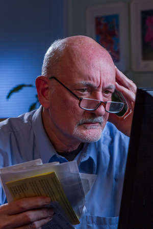 paying bills online: Stressed older man paying bills online, vertical