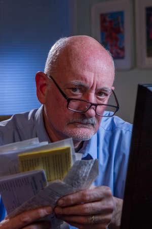 Unhappy older man paying bills online, vertical