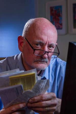 Unhappy older man paying bills online, vertical  photo