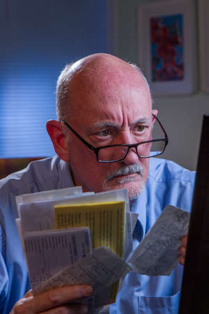 Stressed older man paying bills online, vertical