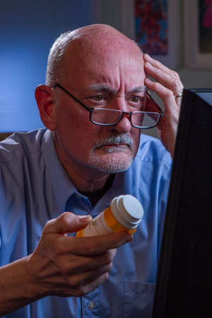Confused older man refilling prescription online, vertical Confused older man refilling prescription online, vertical  Stock Photo