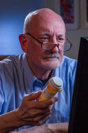 refilling:  Confused older man refilling prescription online, vertical  Confused older man refilling prescription online, vertical