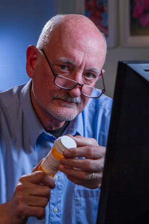Older man holding prescription and using computer