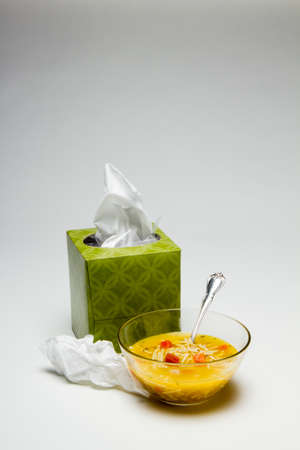 Box of tissue with chicken noodle soup in a bowl