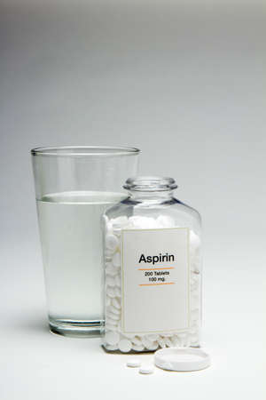 pain killers: Glass of water with bottle of aspirin, vertical Stock Photo