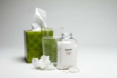 Tissue, glass of water and aspirin bottle, vertical