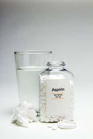 Glass of water and aspirin bottle