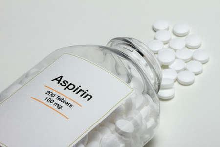Aspirin bottle fallen over with pills Stock Photo
