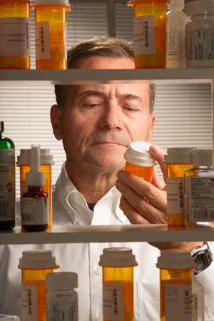 white male looking at assortment of prescription drugs Stock Photo