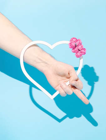 Hand holding white heart frame decorated with pink roses, showing middle finger. Pastel blue background. Minimal creative idea.