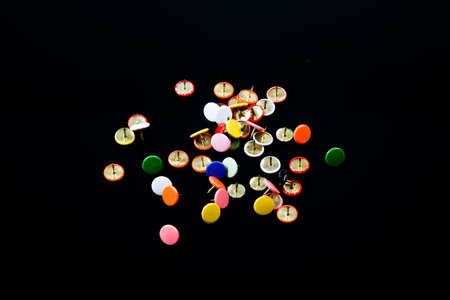 multicolored  isolated pins on black table photo