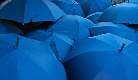 weather protection: background of open blue umbrellas receding into distance Stock Photo