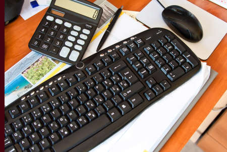 office desk with keyboard, calculator, mouse and pen