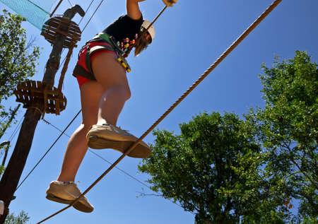 Mädchen klettern mit Sorgfalt in Erlebnispark Editorial