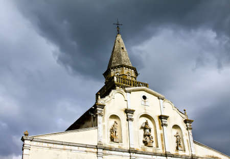 church with bell tower under black clouds photo