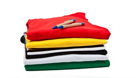 a stack of colorful t shirts and ballpoint pens