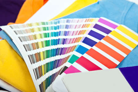 several colorful t-shirts and color scale Standard-Bild