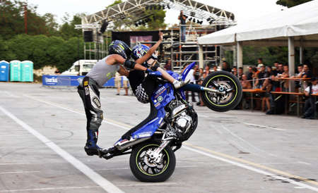Stunt biker standing and girl sitting on handlebar, all on back wheel