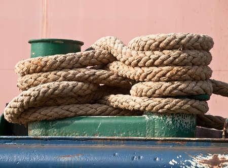 green mooring bollard and bundle of rope photo