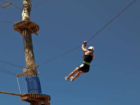 roped: chica joven se desliza en parque de aventuras
