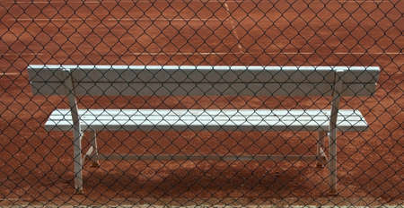 empty tennis court  and white wooden seat