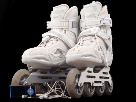 roller skates and mp3 player with headphones isolated on black background Stock Photo