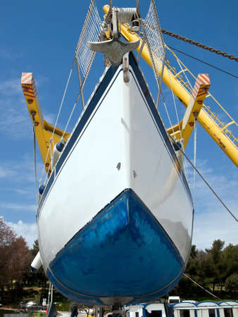 sailboat hanging on crane and preparing for service Stock Photo