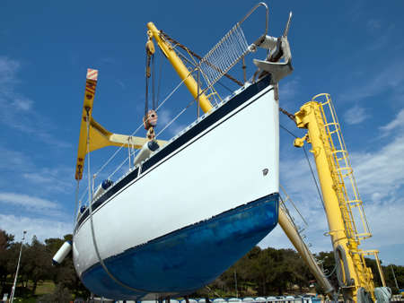 sailboat hanging on crane in harbor service