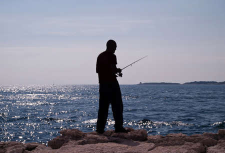 man fishing in the sea - silhouette of a fisherman photo