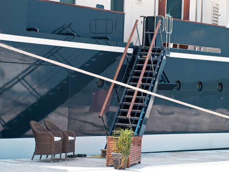 modern yacht moored in the port, gangway and reflection
