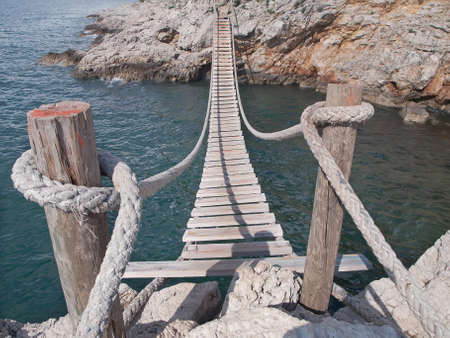 hanging wooden bridge connect rocky seacoast Reklamní fotografie - 21739348