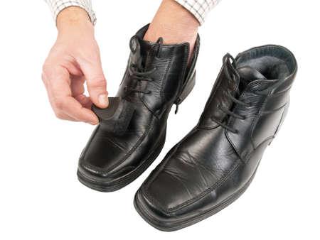 foot ware: man polishing black shoes, isolated on white background, studio shot Stock Photo