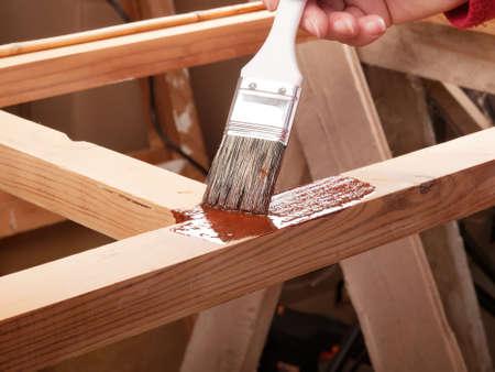 applying protective primer on wooden rack