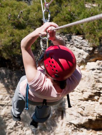 Young girl going across tyrolean traverse Stock Photo