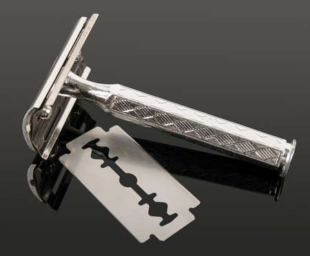vintage razor and blade with reflection isolated on gray background